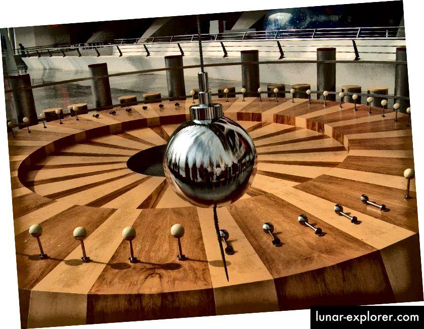 Dieses Foucault-Pendel, das an der Ciudad de las Artes und der Ciencias de Valencia in Málaga, Spanien, in Aktion gezeigt wird, dreht sich im Laufe eines Tages und stößt verschiedene (auf dem Boden gezeigte) Heringe um, während sich die Erde schwingt und dreht . (DANIEL SANCHO / FLICKR)
