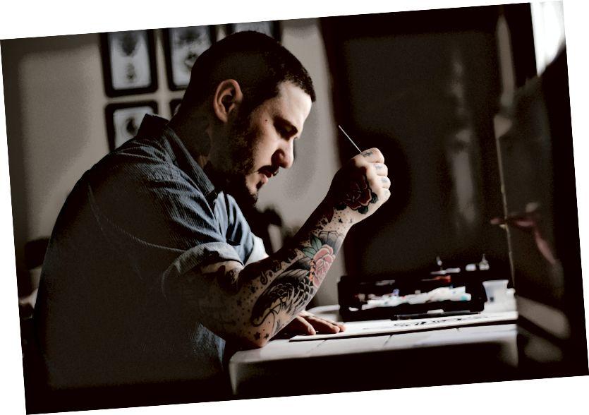 Ալլեֆ Վինիսիուսի «Unsplash» - ի Ալեֆ Վինիսիուսի արված ձեռքին դաջվածքով աշխատող նկարիչը