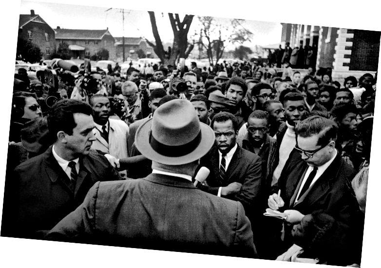 Ուիլսոն Բեյքերը, տեսախցիկով վերադառնալով, հանրային անվտանգության գծով տնօրենը, նախազգուշացնում է գիշերային ցույցերի վտանգների մասին 1965-ի փետրվար 23-ին Սալմա, Ալաբամա նահանգում գտնվող մթնշաղի երթի մեկնարկի սկզբում: Ուղղակի isոն Լյուիսն է Ուսանողական ոչ բռնի հանձնաժողովի կողմից: Լյուիսը մոտ 200 երիտասարդ սևազգեստ ղեկավարեց մոտ երեք բլոկ, այնուհետև վերադարձավ եկեղեցի: (AP Photo) (Անանուն / AP)