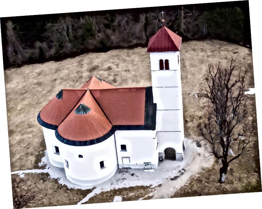 Gereja kecil yang lucu dari St. Volbenk (St. Wolfgang dari Regensburg) dengan apeksnya yang berbentuk kerucut dari abad ke-17. Zelše, Slovenia. Memotret dengan Nikon 1 J1 pada layang-layang delta. Lihat lebih banyak tentang gereja kecil yang unik ini dan sejarahnya di sini.