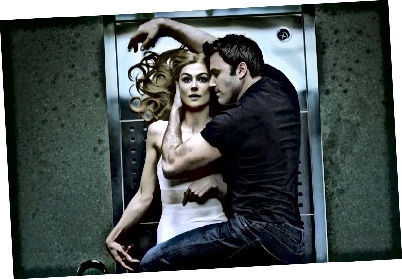 """Rosamund Pike als Amy Dunne neben Ben Affleck als Nick Dunne in """"Gone Girl"""" (2014). Ihr ausdrucksloser, gefrorener Gesichtsausdruck soll die Gefühle der häuslichen Fäulnis zusammenfassen, die sie hat, bevor sie ihren großen Plan entfaltet, ihren Ehemann wegen Mordes zu beschuldigen."""