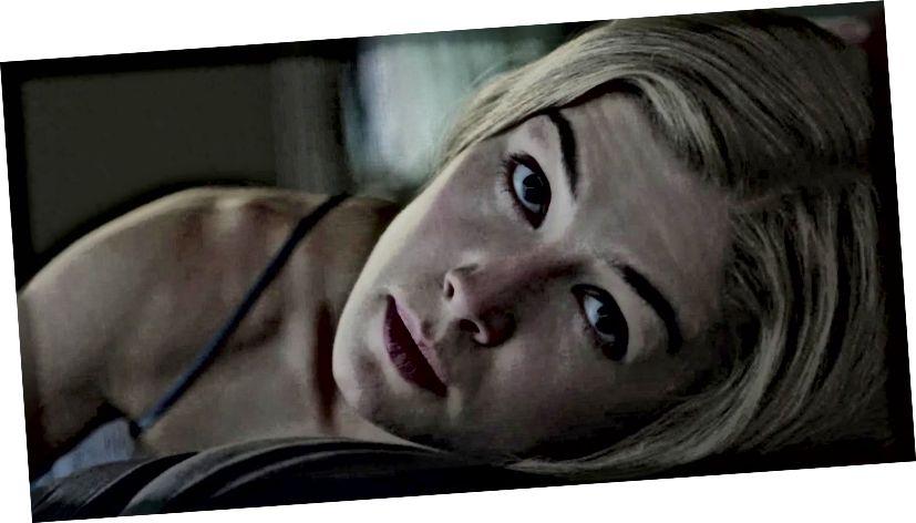 """Rosamund Pike als Amy Dunne in """"Gone Girl"""" (2014). Beachten Sie ihren manipulativen Blick, als sie in diesem Still die Fäden an ihrem unglücklichen Ehemann Nick (Ben Affleck) zieht."""