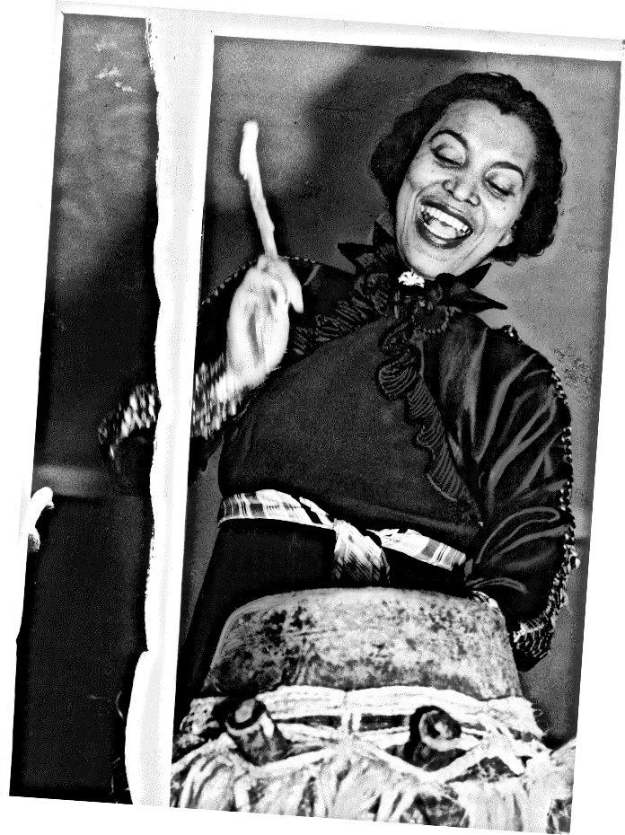 """""""Зора Хърстън, портрет на половин дължина, стояща, обърната леко наляво, биеща хунта или барабан на мама, 1937 г."""" чрез парчето на Черил Ледерле в блога на Библиотеката на Конгреса"""