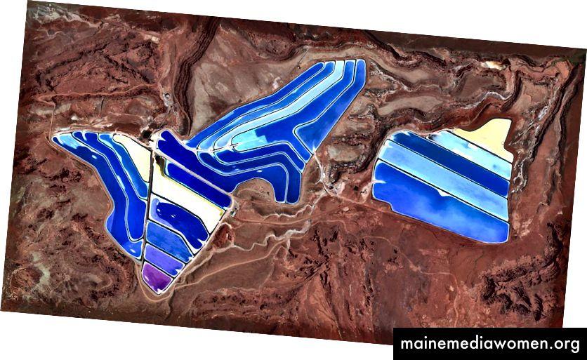 38 · 485579 °, –109 · 684611 ° In der Kalimine in Moab, Utah, USA, sind Verdunstungsteiche sichtbar. Die Mine produziert Kalimurium, ein kaliumhaltiges Salz, das ein Hauptbestandteil von Düngemitteln ist. Das Salz wird aus unterirdischen Solen an die Oberfläche gepumpt und in riesigen Solarteichen getrocknet, die sich vibrierend über die Landschaft erstrecken. Während das Wasser innerhalb von 300 Tagen verdunstet, kristallisieren die Salze aus. Die Farben, die hier zu sehen sind, entstehen, weil das Wasser tiefblau gefärbt ist, da dunkleres Wasser mehr Sonnenlicht und Wärme absorbiert, wodurch die Zeit verringert wird, die das Wasser zum Verdampfen und das Kali zum Kristallisieren braucht. Tagesübersicht | Satellitenbilder © 2016, DigitalGlobe, Inc.