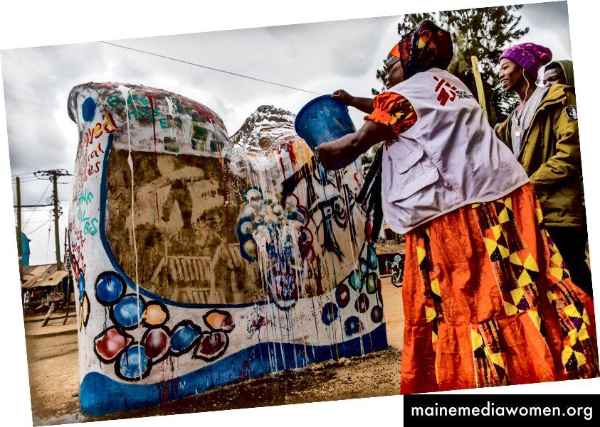"""Siama Musine, MSF-Gesundheitsförderer, malt mit den lokalen Künstlern. Siama arbeitet seit 15 Jahren mit MSF in Kibera. Das MSF-Logo ist in """"unsichtbarer Farbe"""" lackiert, sodass es nur bei Regen im Freien angezeigt wird. Dieses Gleichgewicht zwischen dem Gesehenen und dem Ungesehenen ist ein Symbol für unsere Beziehung zur Gemeinschaft. Auch wenn unsere physische Präsenz in Kibera nicht mehr vorhanden ist, setzt sich der Geist der Priorisierung der Gesundheit, der Behandlung von Menschen ungeachtet ihres Hintergrunds und der Stärkung der Patienten durch die gelebten Erfahrungen unserer Mitmenschen fort hab mich auf dem weg getroffen. Fotos: Bryan Jaybee"""