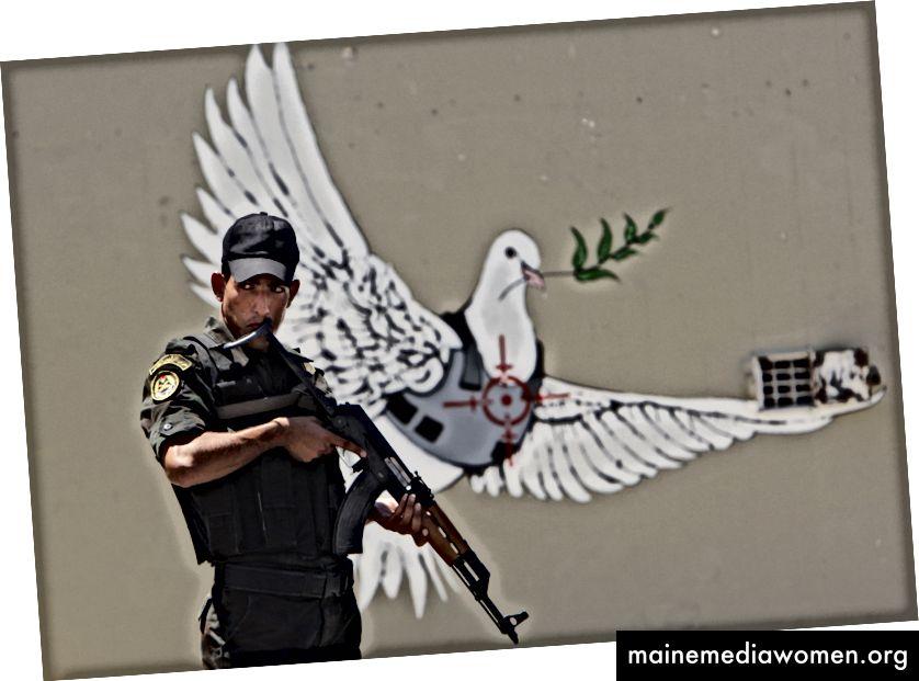Ein palästinensischer Sicherheitsbeamter hält sein Gewehr neben ein Bild, das der britische Künstler Banksy angeblich gemalt hat und das eine Friedenstaube in einer Flakjacke zeigt, bevor der französische Präsident Nicolas Sarkozy am Dienstag, den 24. Juni 2008, in der Stadt Bethlehem im Westjordanland ankommt - AP Foto / Kevin Frayer