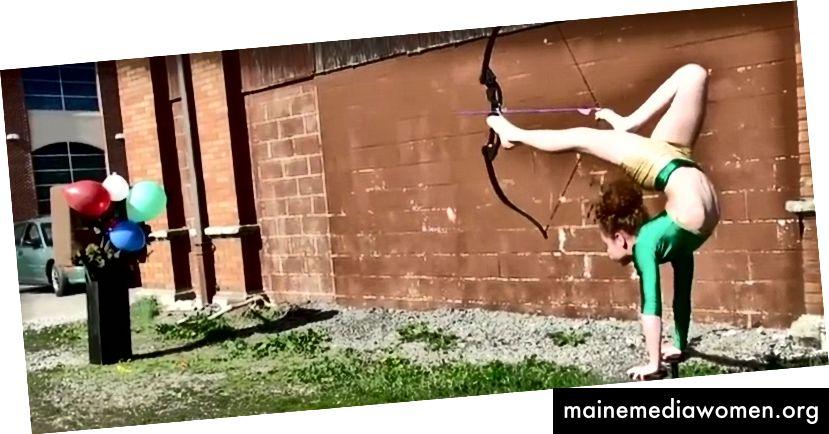 Junges Mädchen übt das Bogenschießen, das auf ihren Händen steht und zeichnet den Bogen mit ihrem Fuß. Aus YouTube-Video aufgenommen.