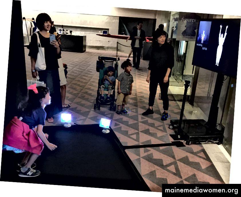 [وصف الصورة: ردهة مكان الأداء مع جهاز عرض على اليمين وصبي صغير على اليسار. يقف الطفل على سجادة سوداء ذات خلفية سوداء تضيءها الأنوار ، وينظر إلى الشاشة ويفسر راقصة على الشاشة. يشاهد الأطفال والعائلة الآخرون الشاشة من الجانب.]