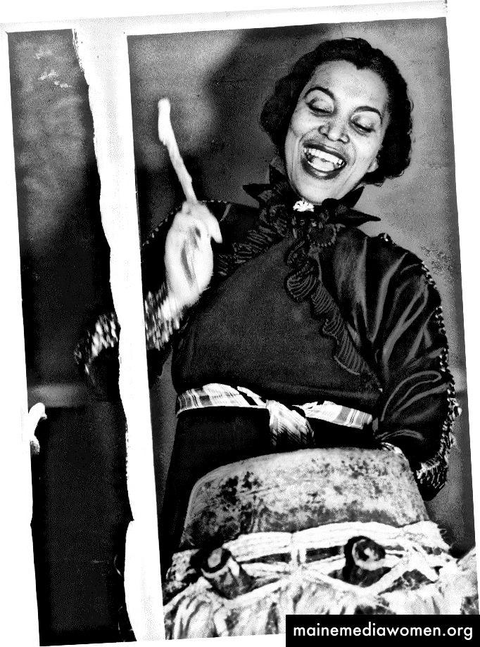 """""""Зора Хърстън, портрет на половин дължина, стояща, обърната леко вляво, биеща хунта или барабан на мама, 1937 г."""" чрез парчето на Черил Ледерле в блога на Библиотеката на Конгреса"""