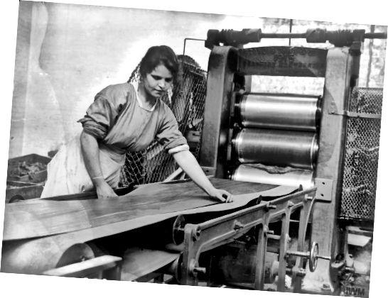 Ένας εργαζόμενος λειτουργεί μια μηχανή ημερολογίου στο εργοστάσιο καουτσούκ των Charles Macintosh and Sons Ltd, Manchester, Αγγλία, Σεπτέμβριος 1918.