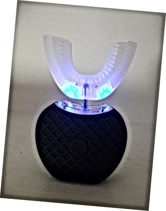 वी-व्हाइट 360 ° इलेक्ट्रिक टूथब्रश। ब्लू लाइट इंगित करती है कि इकाई व्हाइटनिंग मोड में है