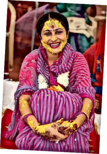 Indická nevěsta s kurkumou na tváři a pažích.