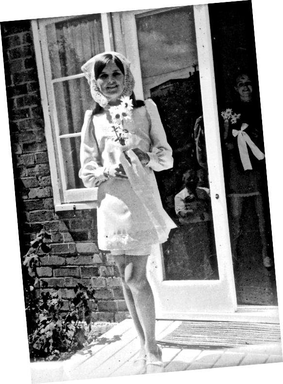 Nevěsta nosí mini šaty, které létají tváří v tvář tradici, její kytice je jednoduchá hrst sedmikrásky.
