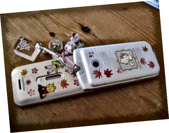 Japonský mobilní telefon z 2000 let zdobený samolepkami Maki-e a několika různými kouzly mobilních telefonů.