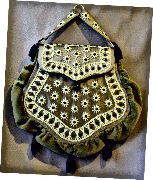 """Tato taška se skládá z buckram rámu, pokrytého vyšitým hedvábným taffetem. Drobné černé skleněné perly z pozdně viktoriánských smutečních šatů zvýrazňují design. Vnější strana je pokryta sametem. Taška, jako je tato, by byla """"uvázána"""" do pasu"""