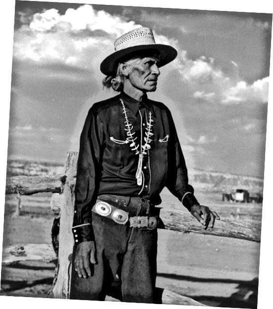 पारंपरिक नवाजो पोशाक में एक बुजुर्ग व्यक्ति के डॉन ब्लेयर द्वारा फोटो जो एक शंख बेल्ट फ़िरोज़ा हार और पुआल टोपी पहने हुए है