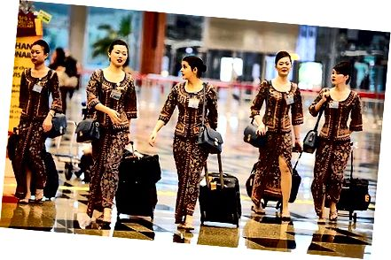 Singapore Airline Flight Attendants in hun figuur knuffelen Sarong Kebaya