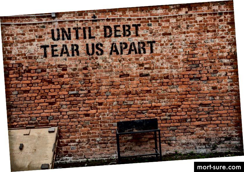 """""""Графитите на стара тухлена стена гласи"""" докато дългът не ни разкъса """"от Алис Паскуал на Unsplash"""