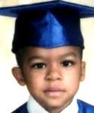صورة لحسني جميل كامبيل ، صبي أمريكي من أصل أفريقي يبلغ من العمر 5 سنوات يرتدي قبعة تخرج من الساتان الأزرق وفي عام 2009.