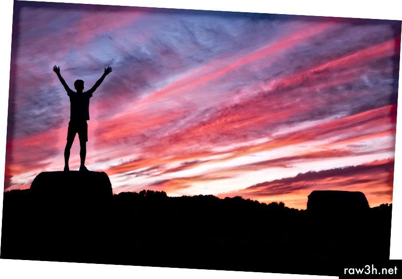 """""""Силует на мъж, който повдига ръцете си, докато стои на скала при изгрев"""" от Бенджамин Дейвис от Unsplash"""