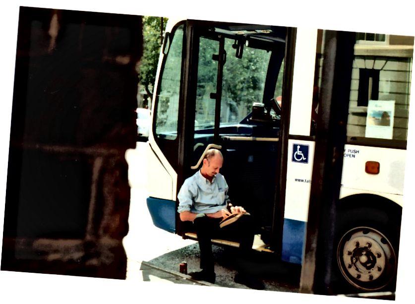 يستمتع سائق الحافلة المحلي الخاص بي بأشعة الشمس الصيفية مع كتاب في متناول اليد