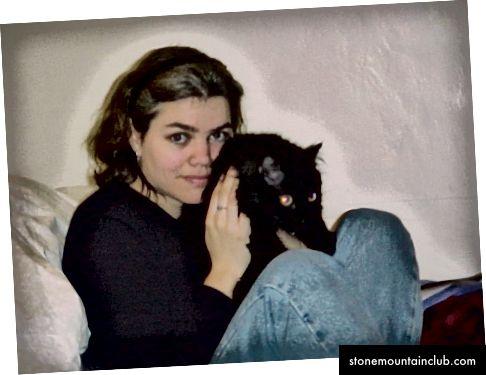 Xotini, yumshoq hamkorlik qiladigan mushuk bilan 1999 yil yanvar. Fotosurat kameraning o'ziga xos echimida.