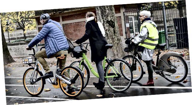 Menschen auf gemeinsamen Fahrrädern in Paris