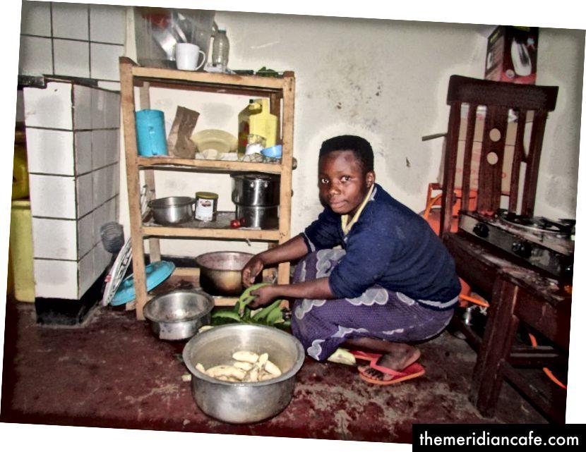 Алиса в кухнята си приготвя обедната храна за семейството си. Зад нея е газовата печка, която обикновено използва за готвене. Снимка на Xaver Rukundo.