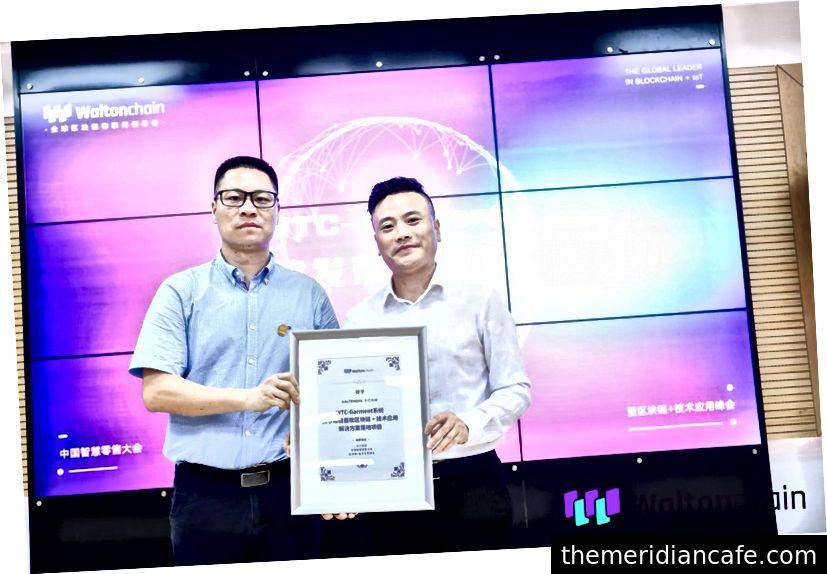 O COO da Waltonchain, Monitor Chan (à esquerda) apresenta o sistema WTC-Garment ao diretor do Centro de Produtos Kaltendin, Zhang Zhengxiong