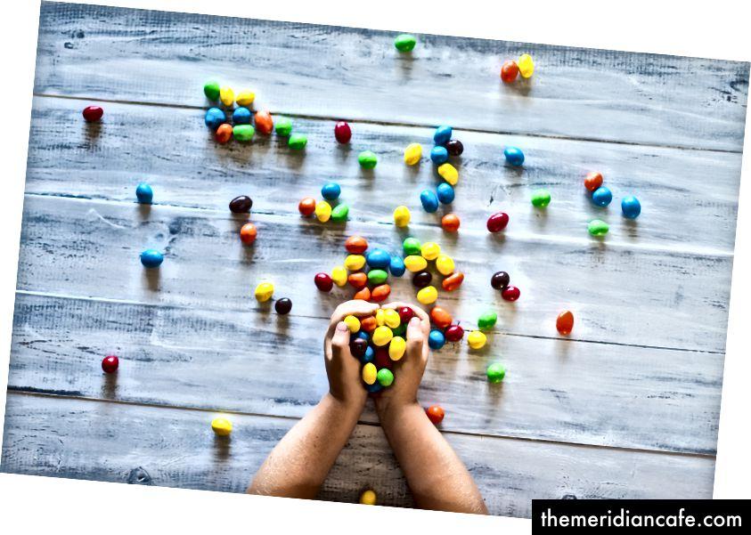 """""""Foto seletiva de criança segurando doces na palete de madeira cinza"""" por Patrick Fore na Unsplash"""