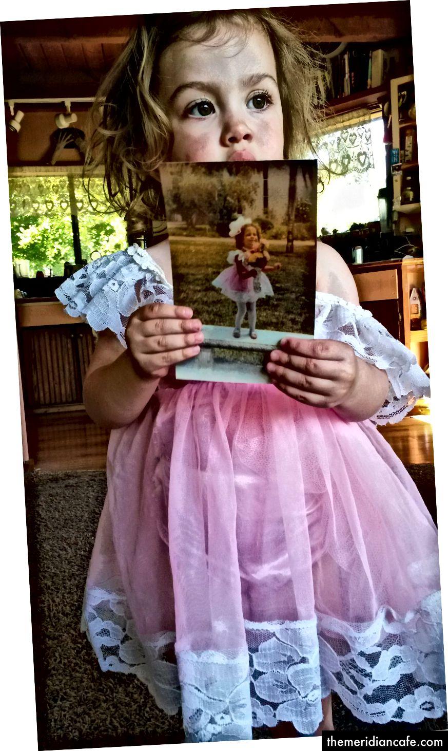 Minha filha, usando meu vestido antigo de recital, segurando uma foto minha comigo de 3 anos no dia do recital. (Crédito da foto: autor)