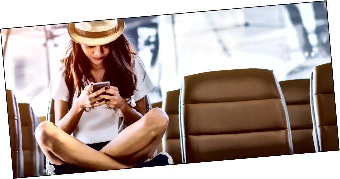 Маладая жанчына, выкарыстоўваючы свой тэлефон у аэрапорце
