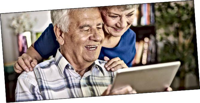 Parella de gent gran somrient mentre juga amb una tauleta