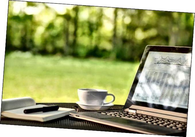 Ноўтбук і кава на стале на адкрытым паветры