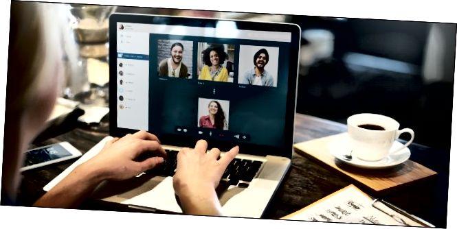 Рукі жанчыны на клавіятуры яе ноўтбука з чатырма людзьмі ў відэаканферэнцыі на экране.