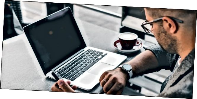 Ένας άντρας σε ένα τραπέζι σε μια καφετέρια κοιτάζοντας το ρολόι του με το φορητό του ανοιχτό μπροστά του.