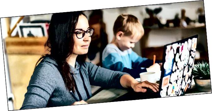 Жанчына працуе на ноўтбуку з дзіцем, які сядзіць побач з яе малюнкам.