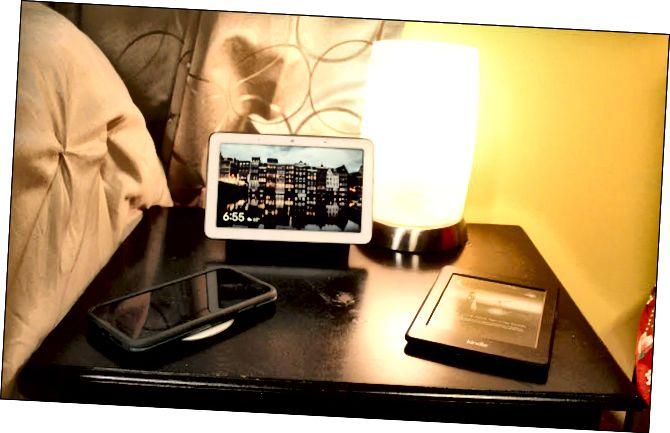 Un Nest Hub, carregador sense fils, llum amb bombeta intel·ligent i encesa.