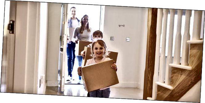 Una família feliç que porta caixes a casa.