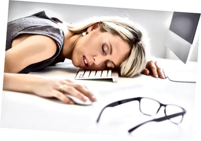 אישה מותשת ישנה מול המחשב