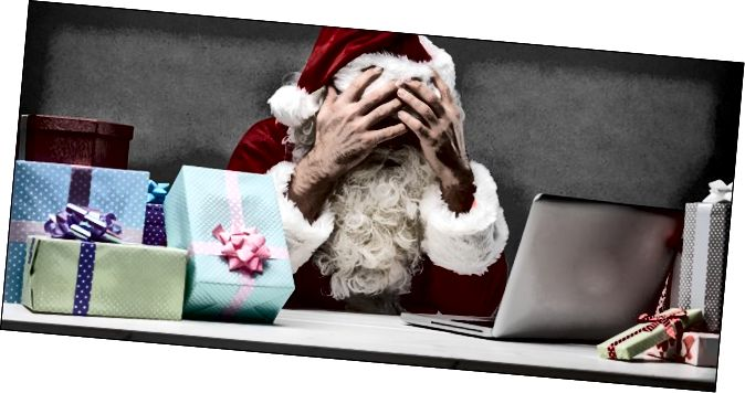 산타 그의 손으로 그의 얼굴을 덮고 그의 노트북 및 선물의 스택 앞에 앉아.